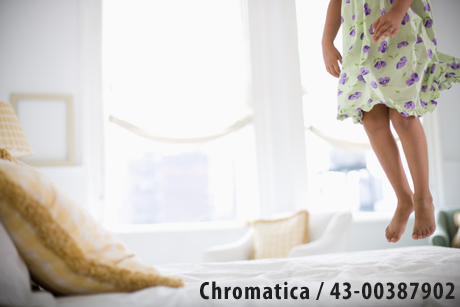 Low section view of young woman jumping on bed - Chromatica